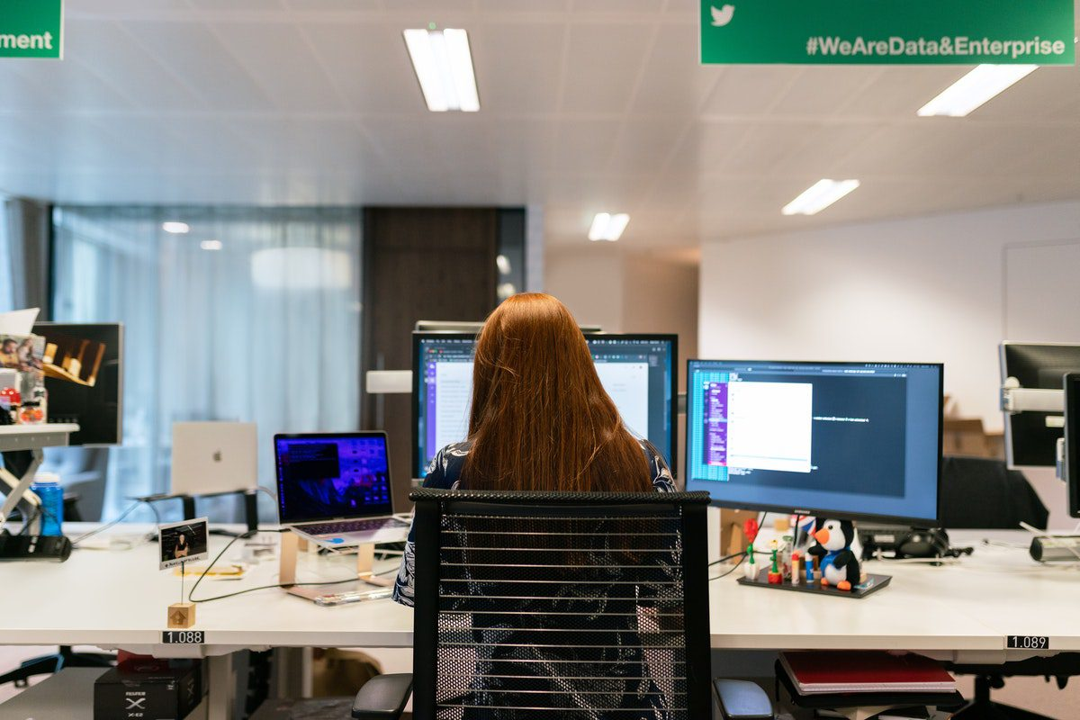 woman working on multiple personal projects on several computer screens How to Become a Data Engineer