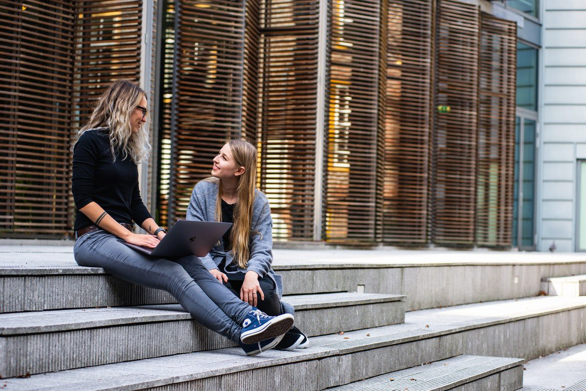 Two women having a conversation on stairs How to Become a Sales Development Representative