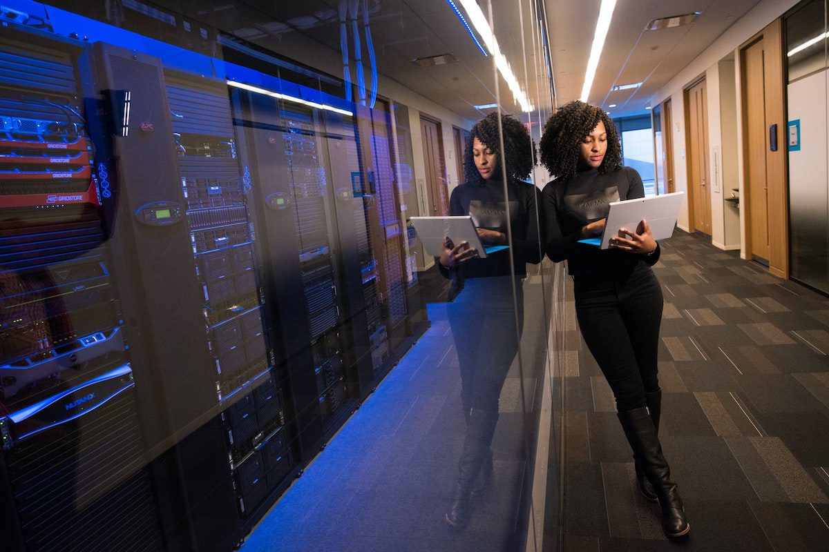 A woman holding a laptop stands by a room full of machines. How to Become a Systems Analyst