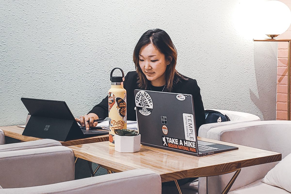 Woman sitting at a corner table with a black Microsoft laptop in front of her. You can also see a water bottle, wall decorations, and a trendy Windows laptop next to her. Apprenticeships Microsoft