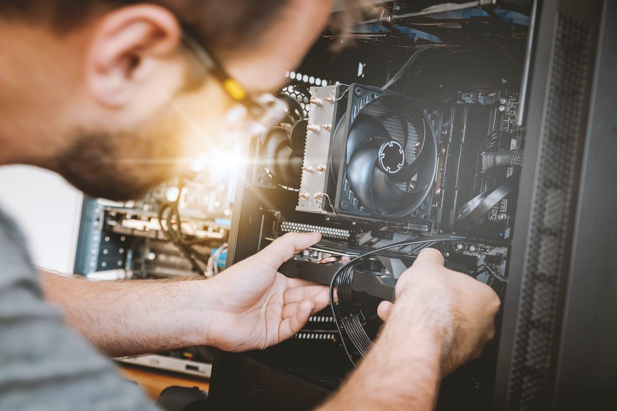 A man installs hardware into a machine. How to Become a Systems Analyst