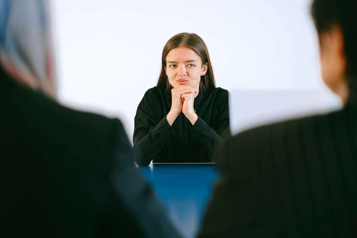 a woman in an interview pondering her answer to a follow-up question Chemical Engineer Interview Questions and Answers