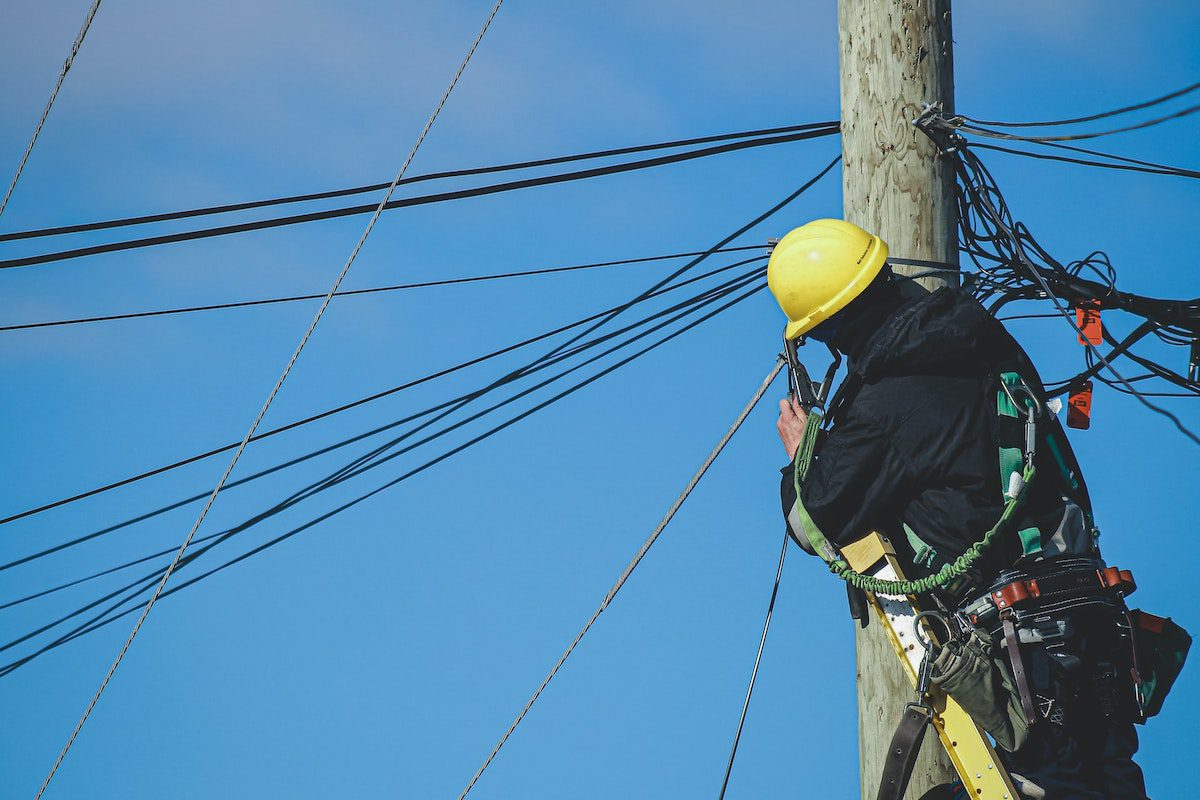 A man wearing a yellow helmet and tool belt standing at the top of a telephone pole, fixing power lines How to Become an Electrical Engineer