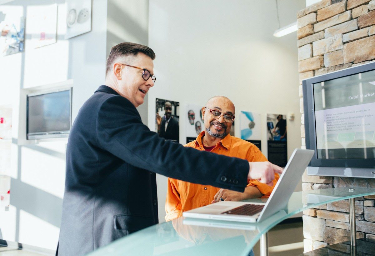 Salesman showing something to another man on his laptop account representative meaning