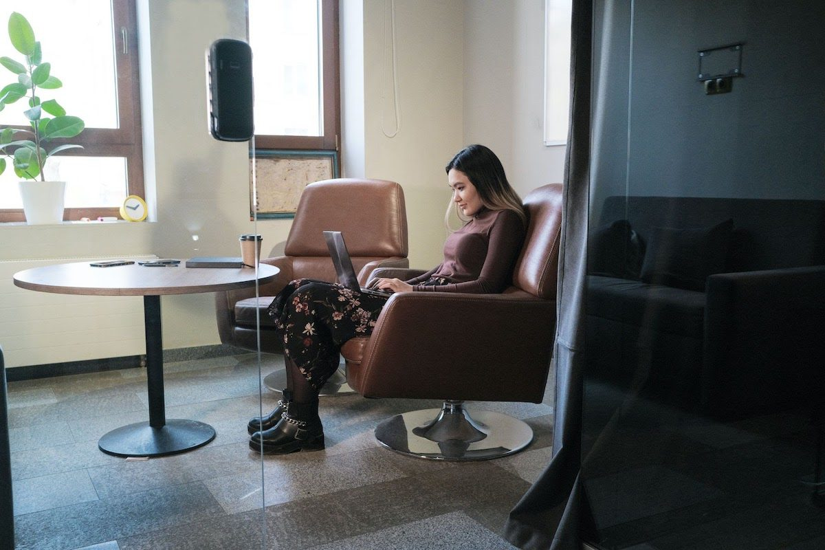 A woman using a laptop while sitting on an armchair in an office how to become an applications architect