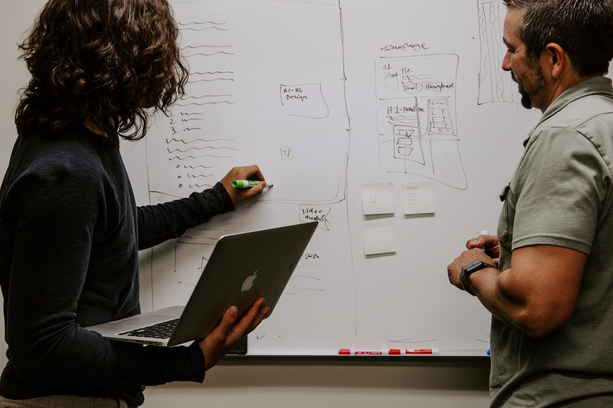 Two men in front of a whiteboard how to become a marketing analyst