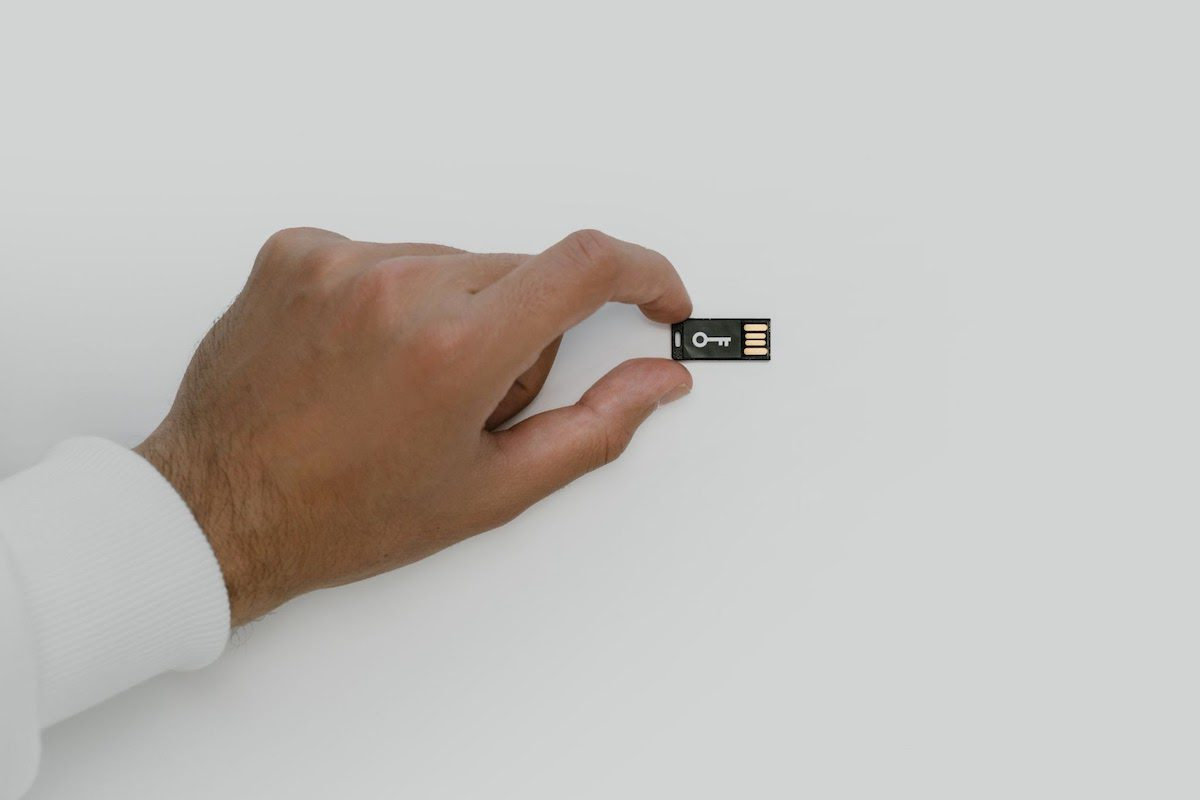 Man holding a USB flash drive with the picture of a key network security analyst