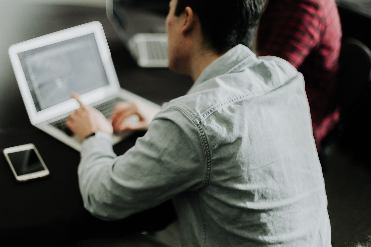 person looking at his laptop how to become a research analyst