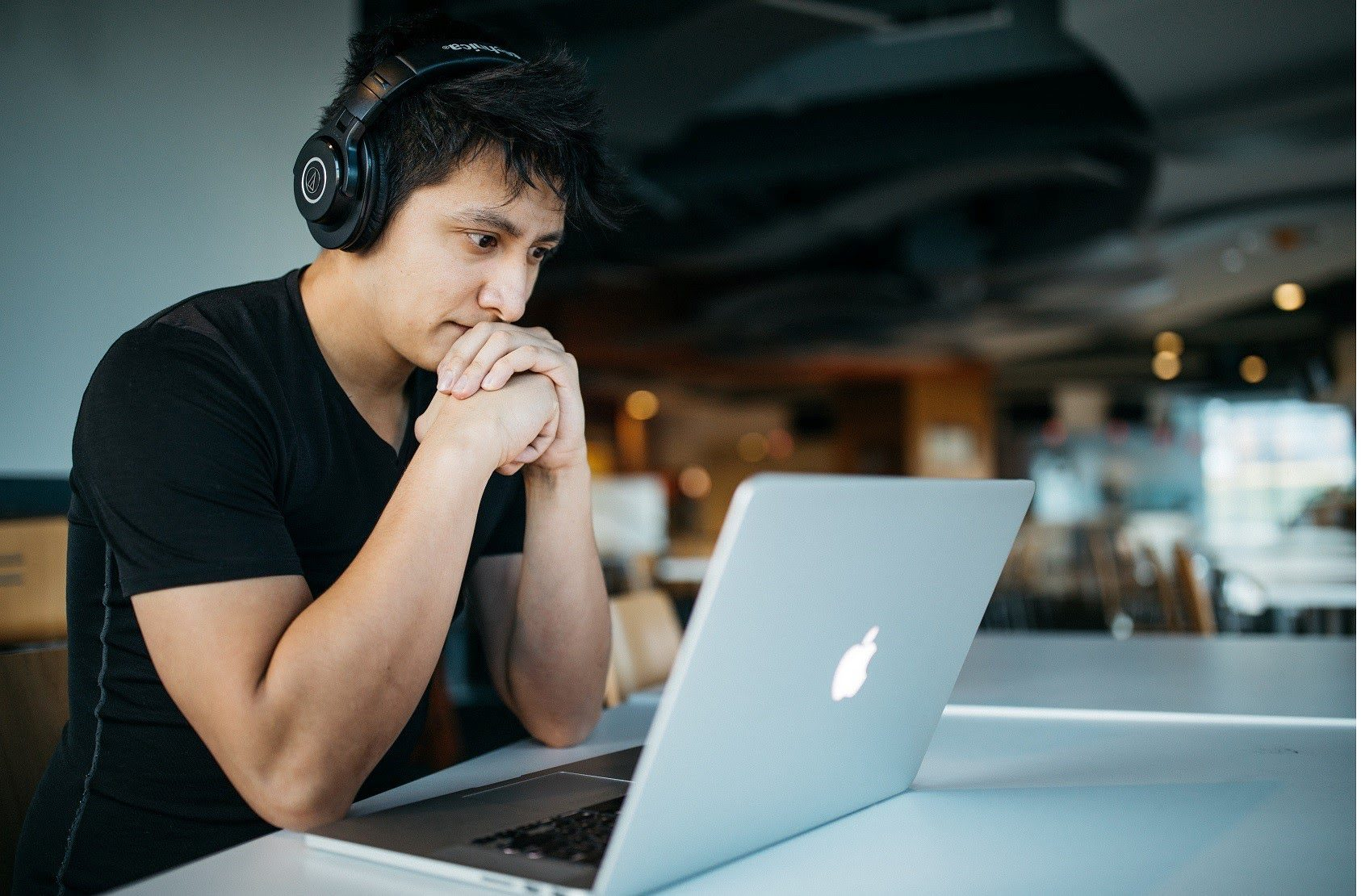 Man wearing headphones looking at a MacBook How To Find An Apprenticeship