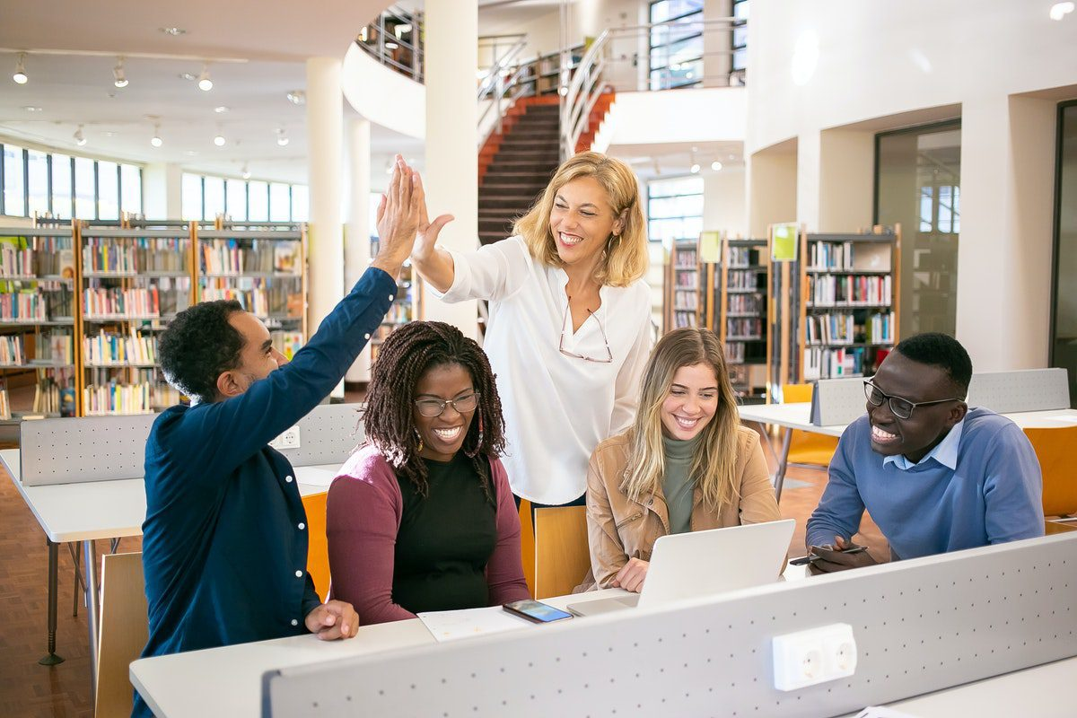 Group of happy students in a library with one person giving the teacher a high five how to become a financial analyst