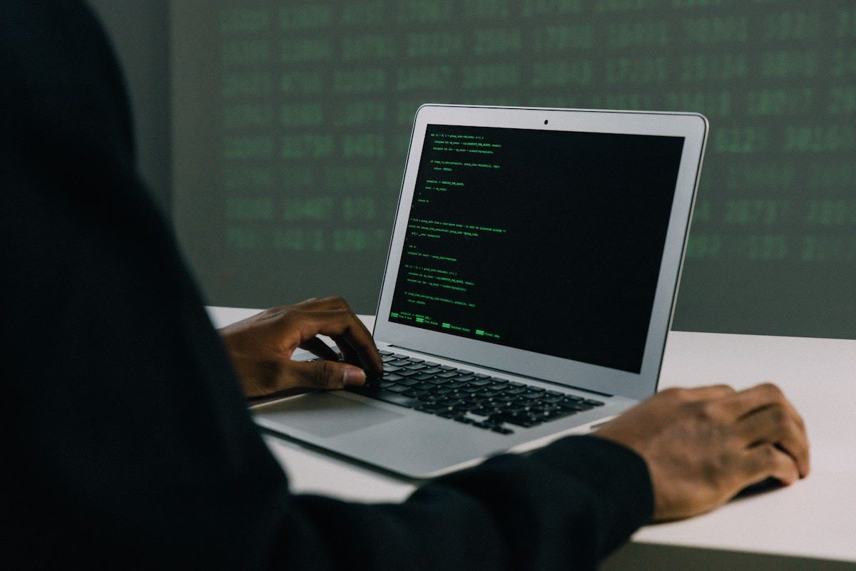 Person using a computer displaying lines of code in green how to become a network security analyst