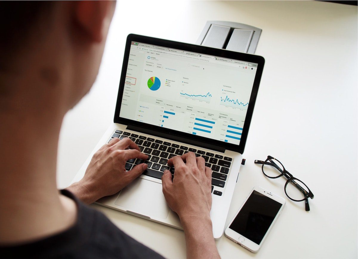 A person using a Macbook how to become a marketing analyst