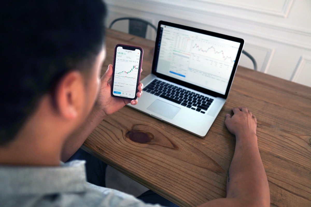 A man studying a progression graph on his iPhone and Macbook How to Become a Quantitative Analyst