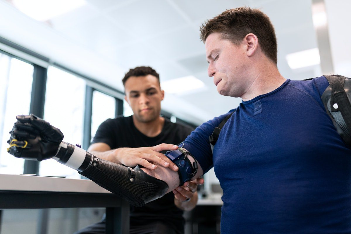 An engineer fitting a prosthetic arm on a male patient how to become a robotics engineer