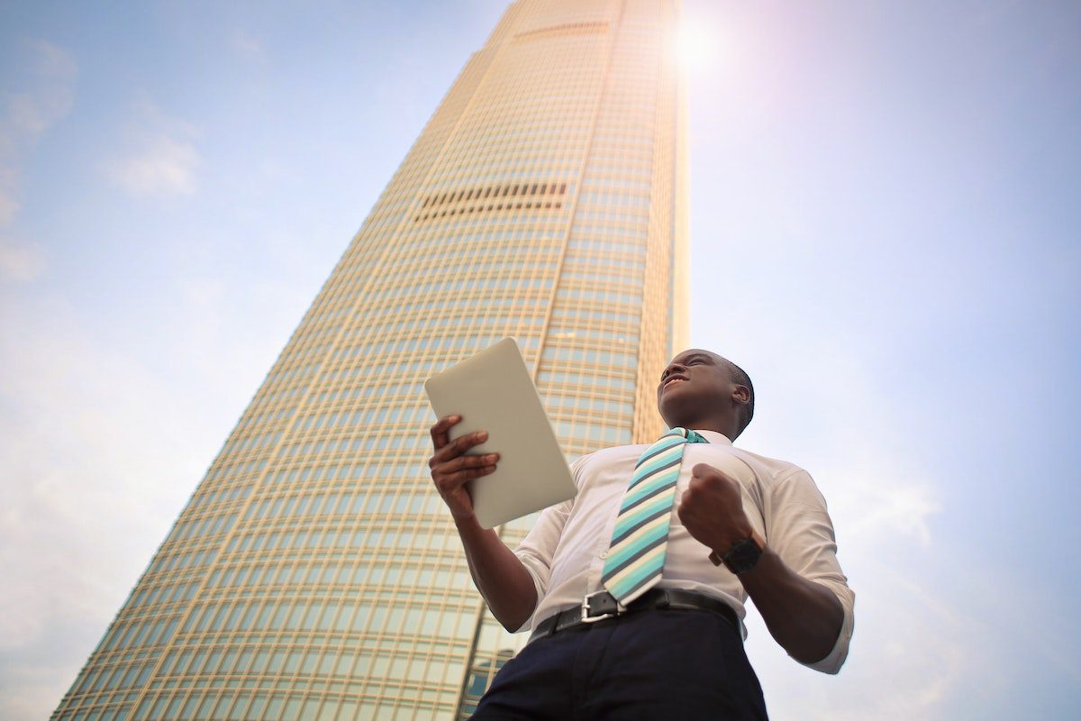 a person in a business analyst career standing beneath a skyscraper. Business Analytics Associate Degrees