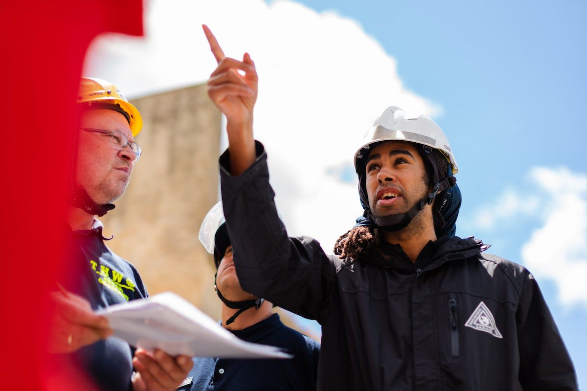 Three engineers sharing ideas at a construction site. Civil Engineer Interview Questions and Answers