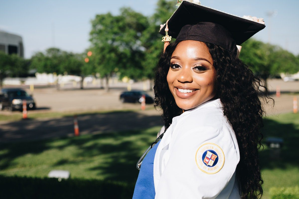 Woman wearing a mortarboard hat smiling to the camera. Computer Programming Associate Degrees