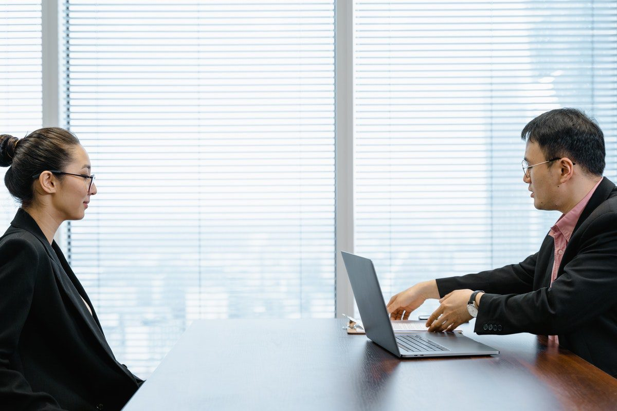 A man at a desk with a laptop interviewing a woman wearing glasses how to get a job in devops