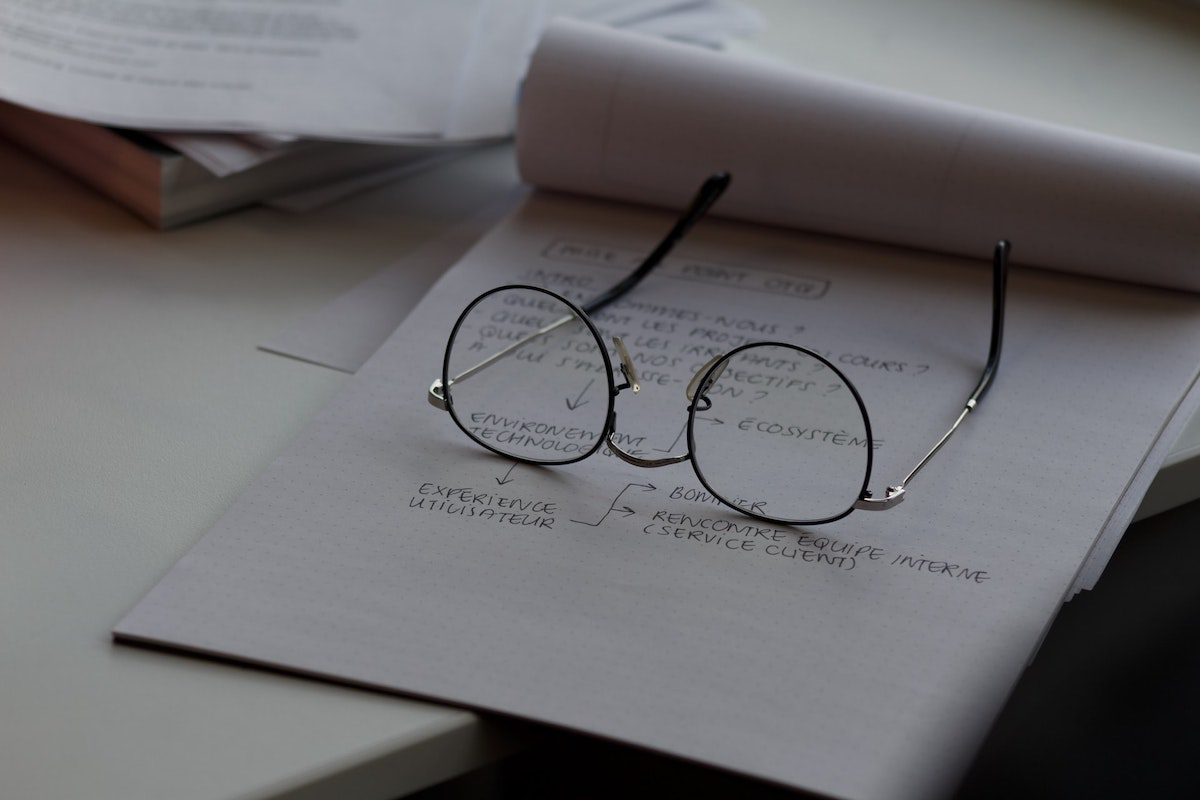 Glasses sitting on a page of notes. Project Management Associate Degrees