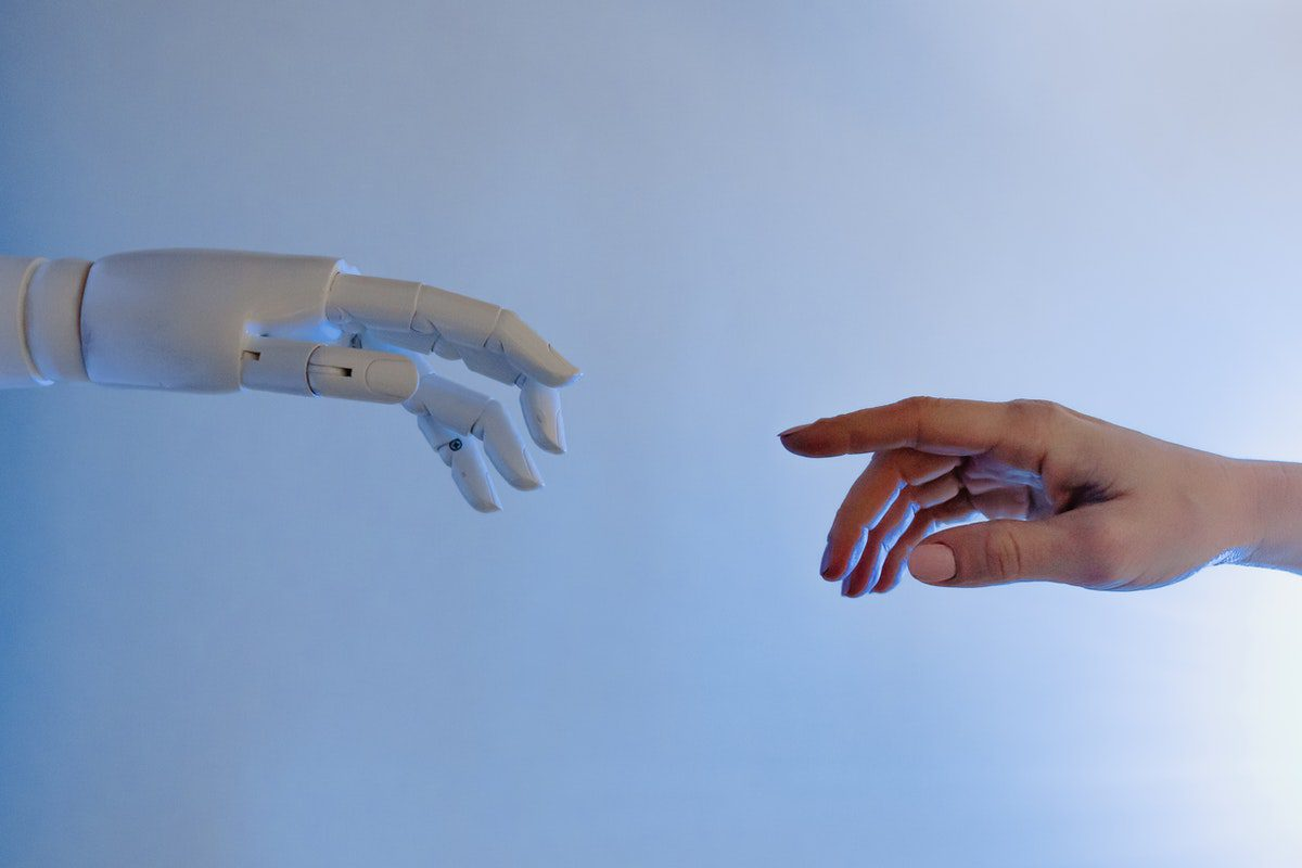 a human hand and a robotic hand trying to touch each other. Robotics Associate Degrees
