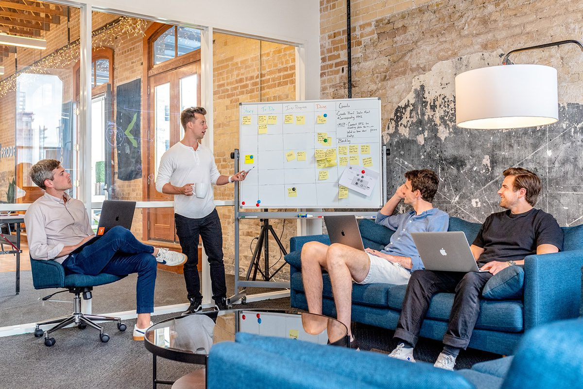 three men sitting with their laptops while a fourth man walks through a sales goal on a whiteboard. Sales Manager Interview Questions and Answers