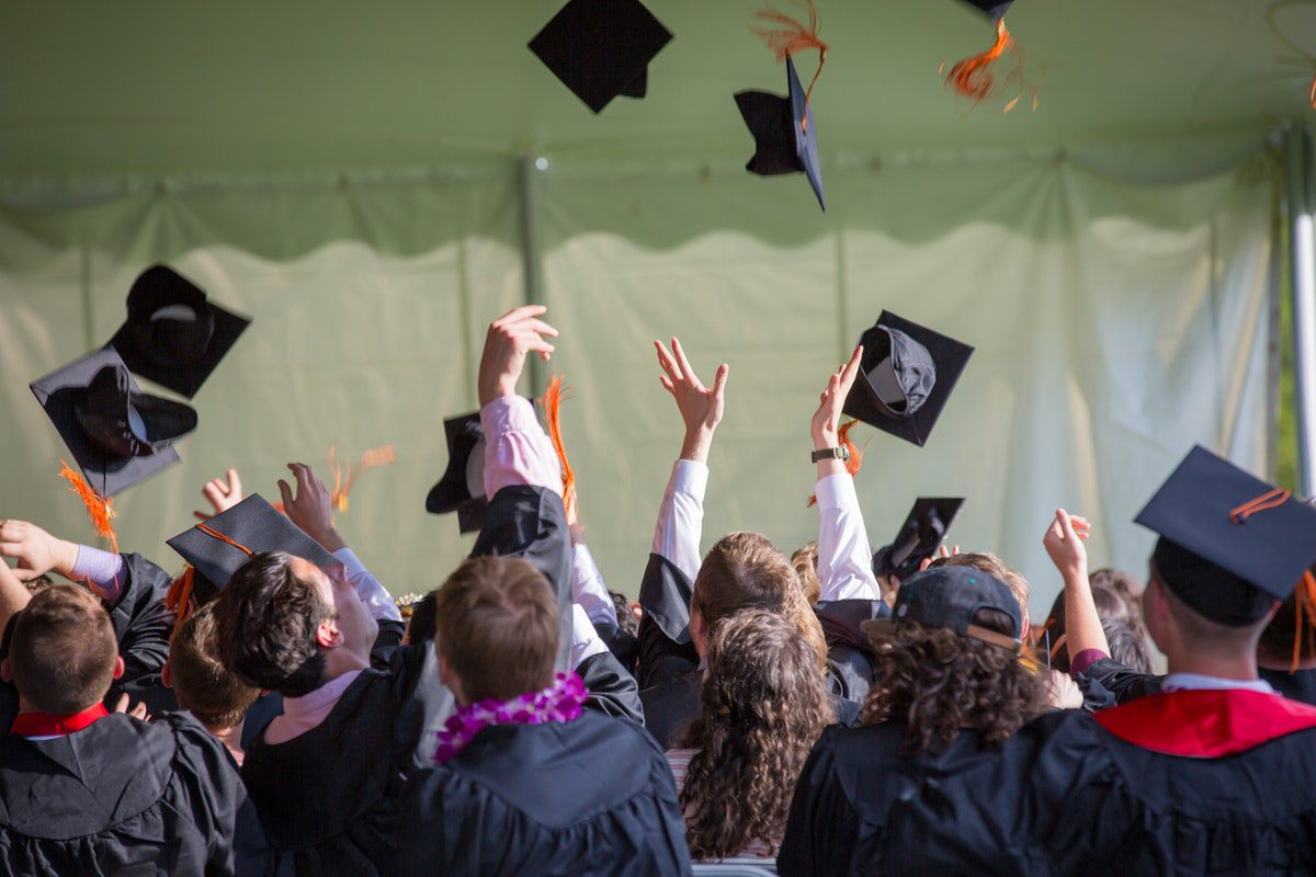 Graduating students throwing their mortarboard hats into the air. Software Engineering Bachelor's Degrees