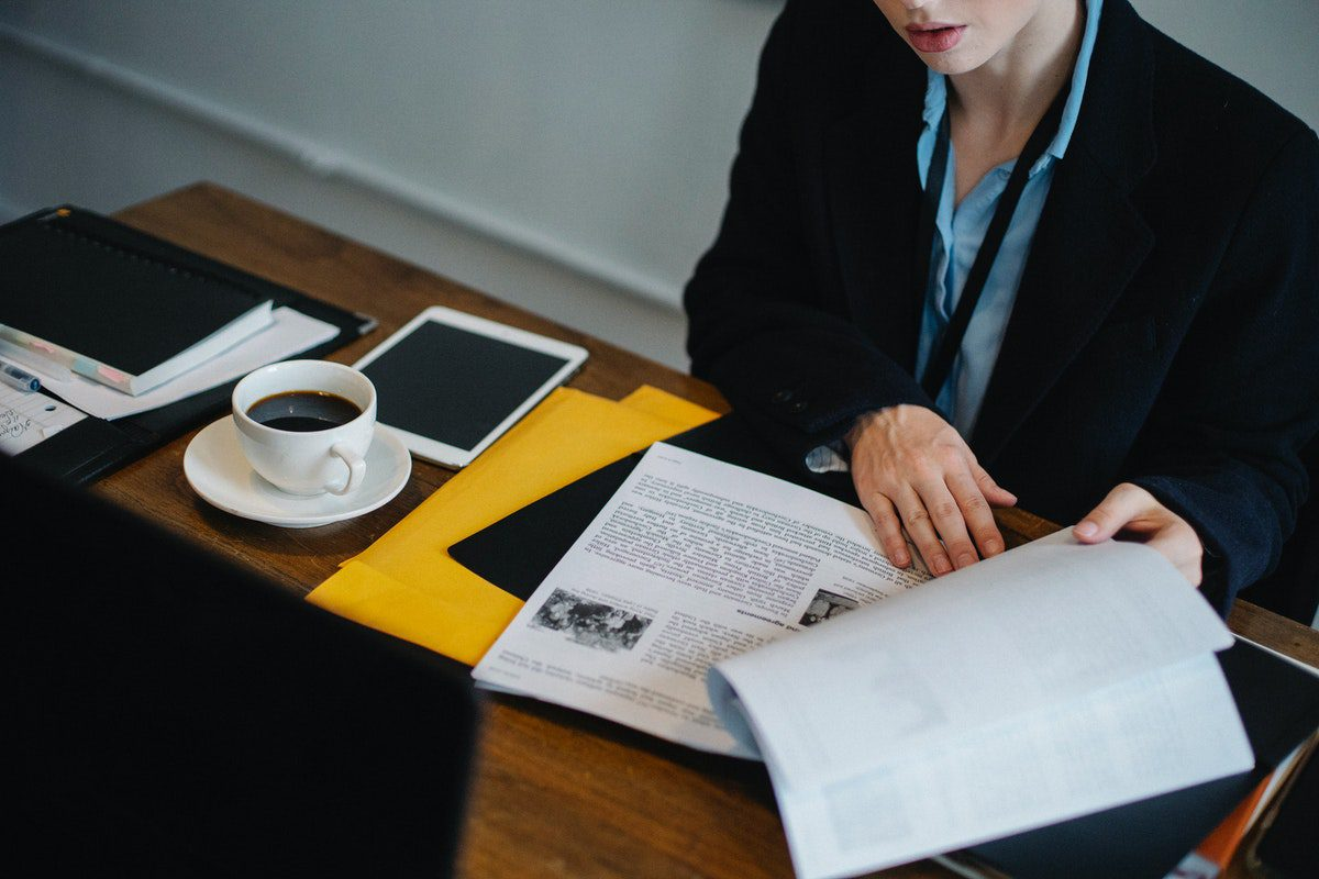 a woman drinking coffee while going through a business process analysis. Business Analyst Interview Questions and Answers