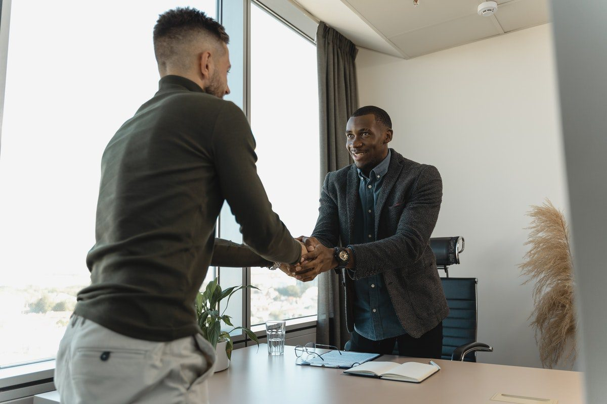 Two men shaking hands while standing up. Copywriter Interview Questions and Answers