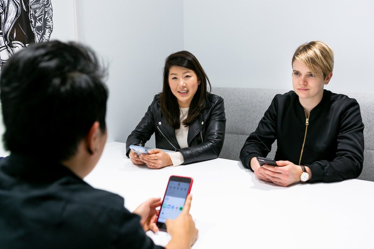 Three adults having a conversation during an interview. Creative Director Interview Questions and Answers