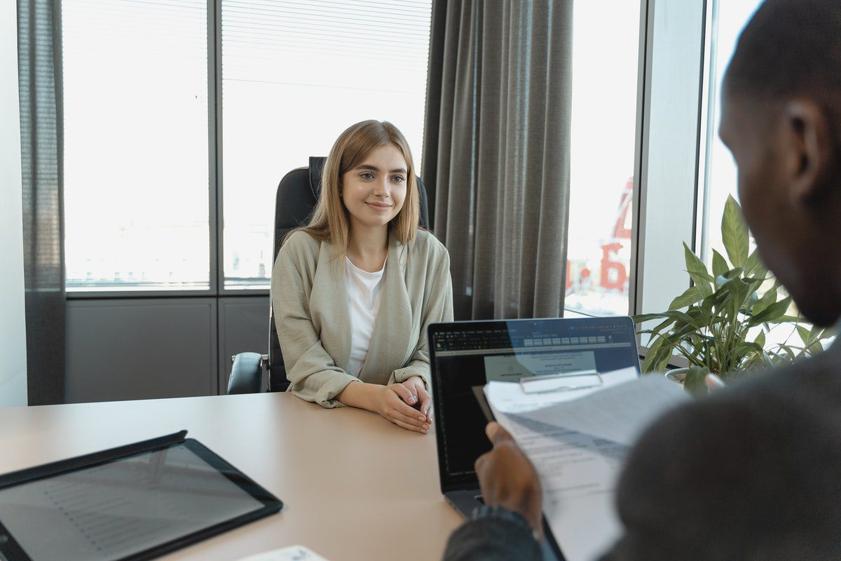 a woman sitting across from a male interviewer as he reviews her resume. Database Administrator Interview Questions and Answers