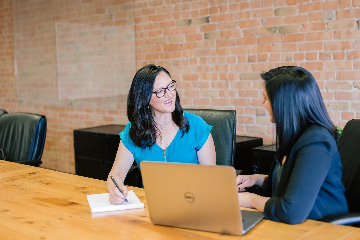 Two smiling women with a laptop on the table. Sales Coordinator Interview Questions and Answers