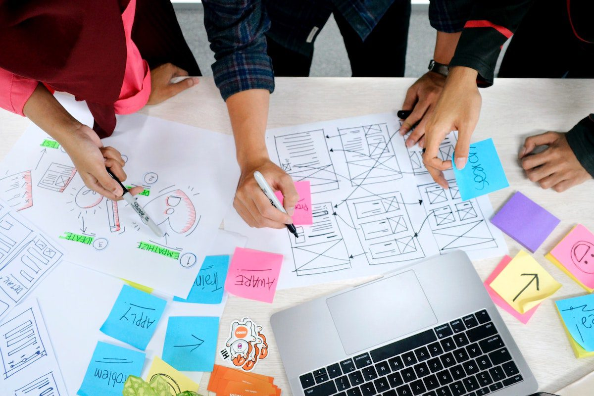 Three people are gathered around a table filled with design plans and notes. UX Designer Interview Questions and Answers