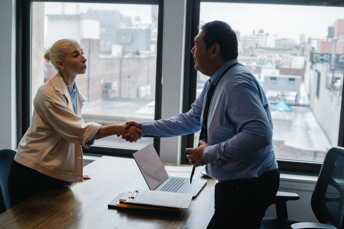 A woman shaking a man's hand in an office. Accountant Interview Questions and Answers