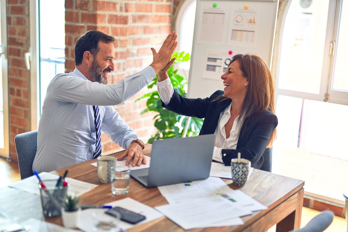 A man and woman smiling and giving a high five in an office. Administrative Assistant Interview Questions and Answers