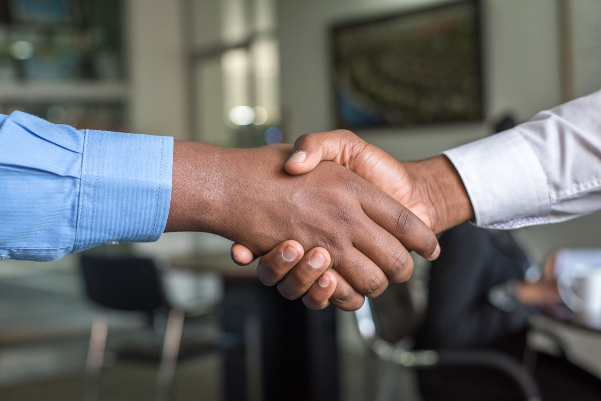 Two people shaking hands. IT Manager Interview Questions and Answers