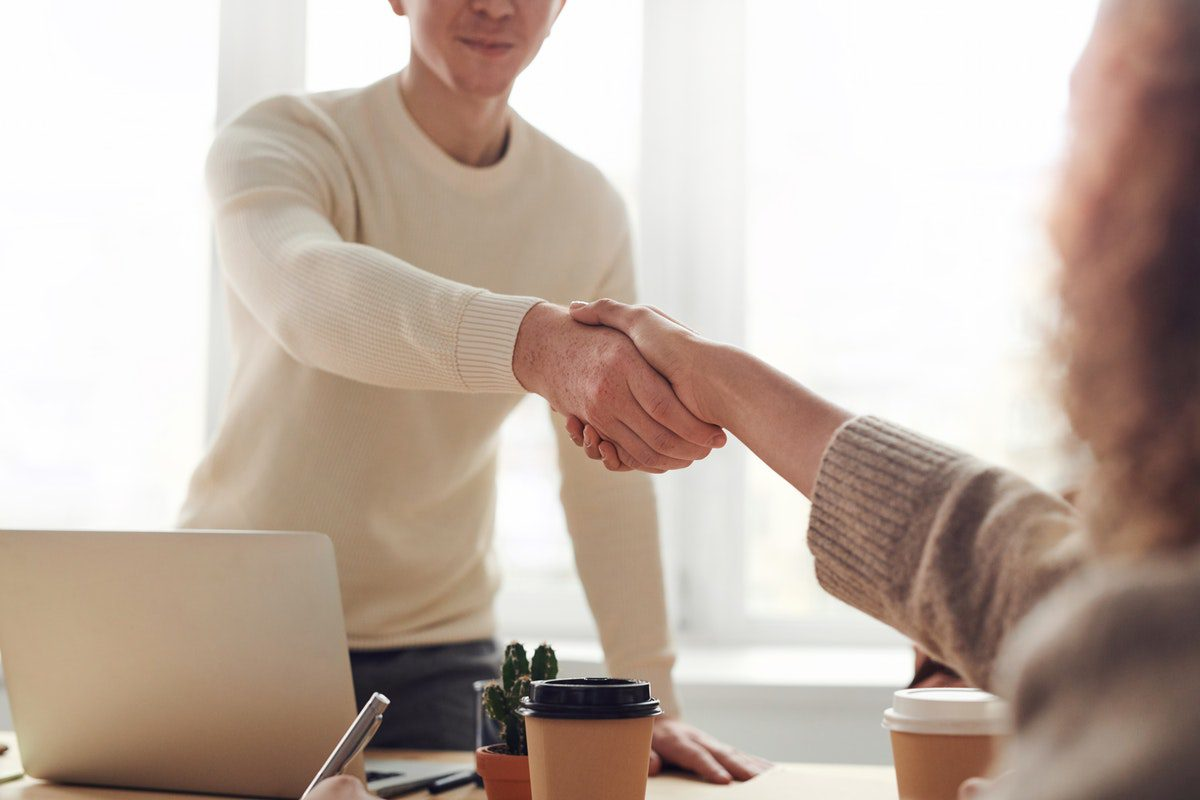 Man and woman shaking hands after a formal meeting. Industrial Engineer Interview Questions and Answers
