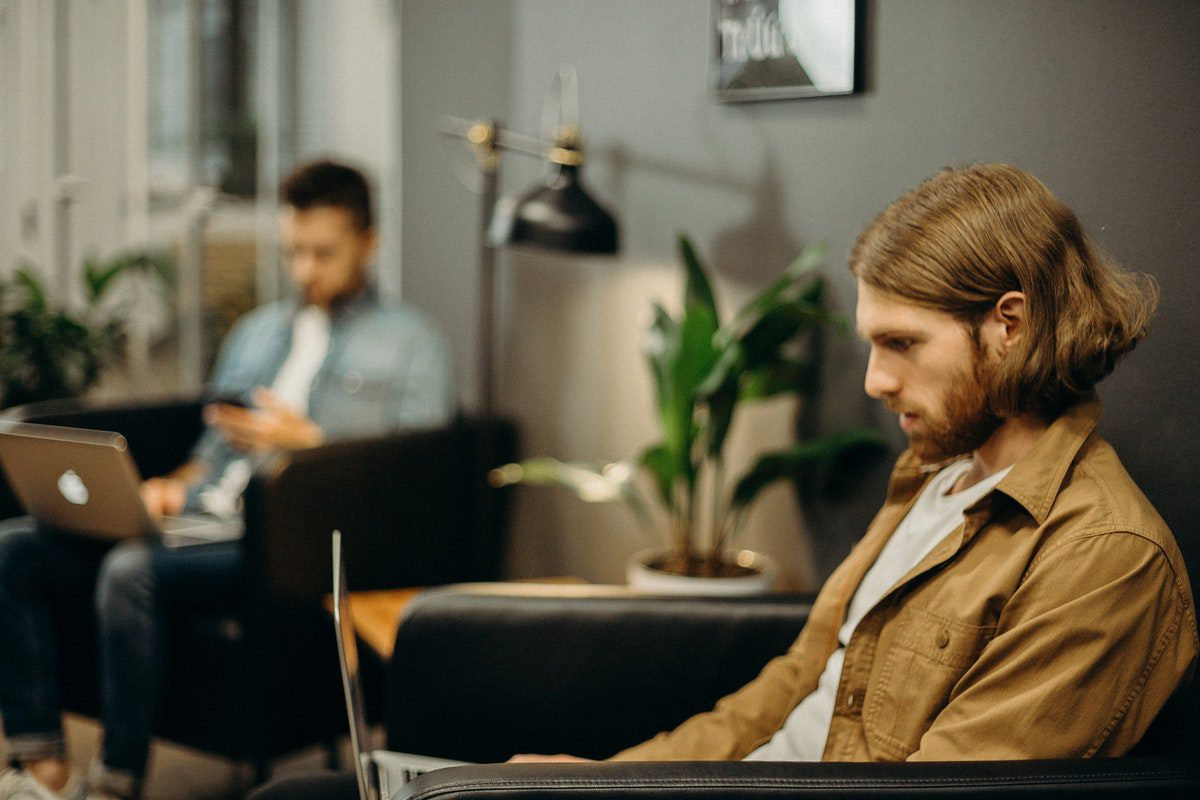 Man in a brown jacket sitting on an armchair using a laptop. Mobile Development Associate Degrees