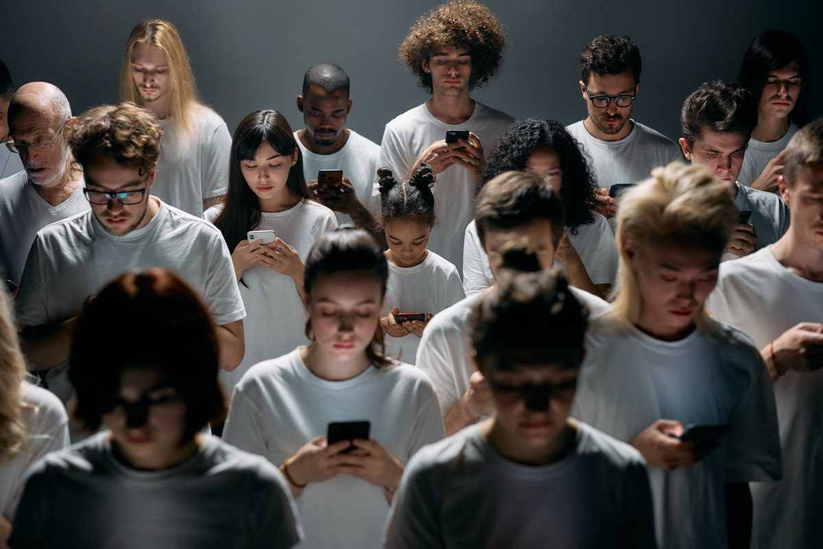 A group of people focused on their mobile phones. UX Designer Interview Questions and Answers