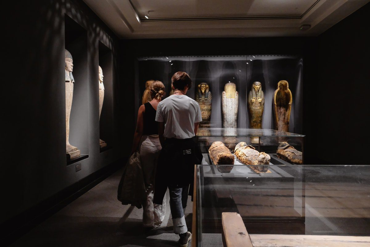 Two people are observing mummies and other historical artifacts inside a museum. jobs for history majors
