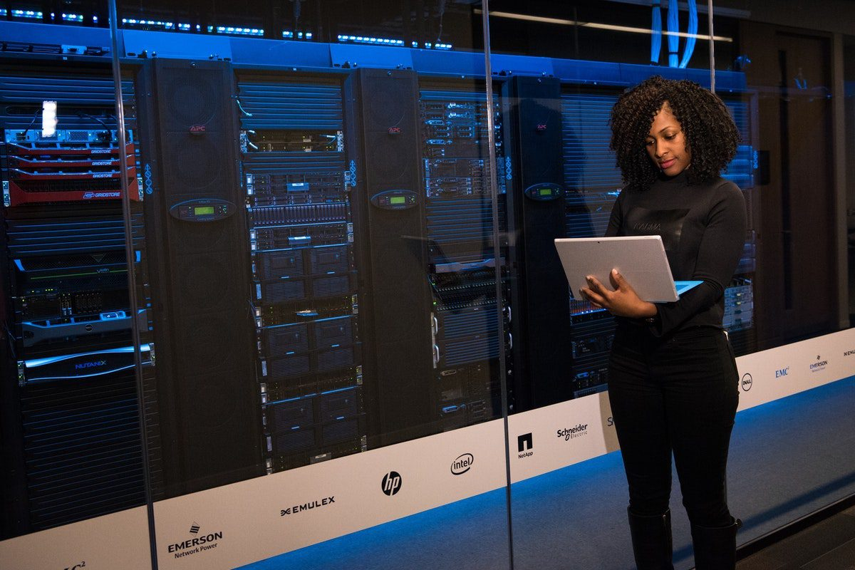 Woman standing next to a database server room. Database Administration Master's Degrees