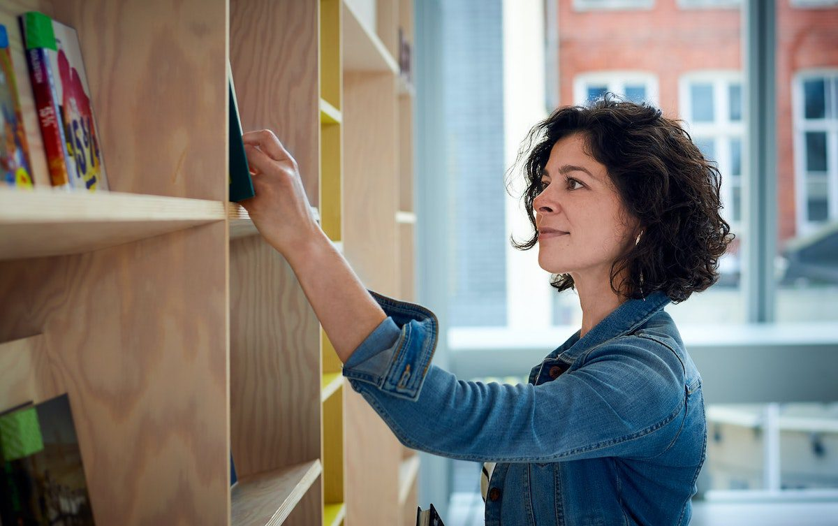 Woman browsing a bookshelf at a library. jobs for english majors