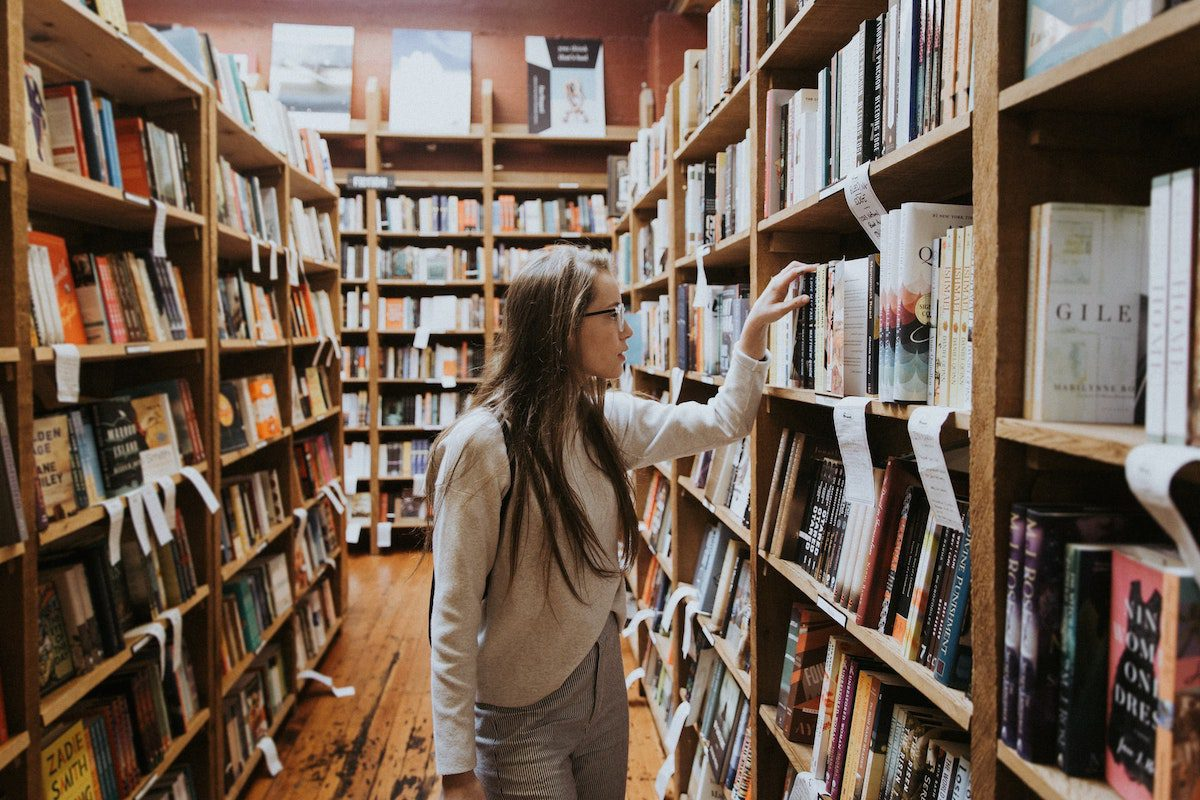 Women standing in a library looking at a shelf full of books. jobs for psychology majors