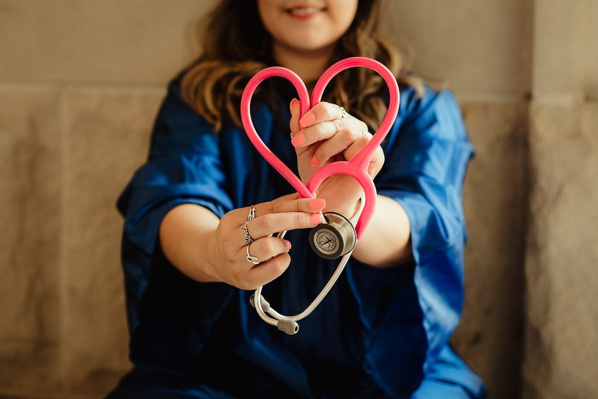 Woman in blue graduation gown holding a pink stethoscope in the shape of a heart Medical Assisting Bachelor's Degrees