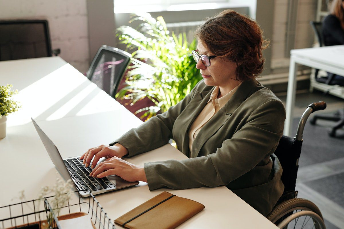 Woman sitting at a desk working on a laptop. Systems Analysis Bachelor's Degrees